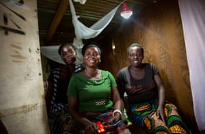 Anick Lubinda (centre) sits at home with her daughter, Judith (left) and niece, Betha (right) in their home village of Mukwalantila near Zimba, Zambia. As well as the bike, the scheme package includes a smartphone to share and access information, a torch to ride safely at night and a solar lamp that Judith (above), can use to do her homework in the evenings.