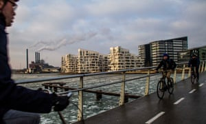 Cyclists cross a bridge from Islands Brygge in Copenhagen with the Oersted gas fired power station in the distance