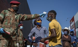 South African National Defense Forces check people's temperature in Johannesburg's Alexandra township on 20 May 2020.