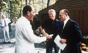 Anwar al-Sadat shakes hands with Menachem Begin as Jimmy Carter looks on, at Camp David in September 1978.
