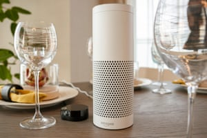an amazon echo on a dinner table with wine glasses