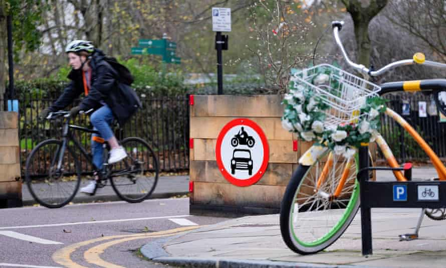 A cyclist passes a wooden planter restricting access to cars and motorbikes into a low-traffic neighbourhood in London