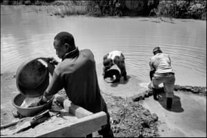 Miners working at a flooded opencast pit at the Busia United mine pan and wash for gold