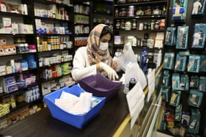 A pharmacist wearing a face mask works in western Tehran.