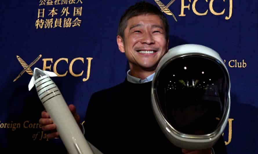 Yusaku Maezawa with model rocket and space helmet