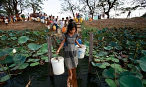 People line up to collect water at Yazarthingyan lake in Dala township, near Yangon, Myanmar.