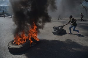 A demonstrator prepares to torch a tyre on the fourth day of protests against Haitian president Jovenel Moise and the misuse of Petrocaribe funds.
