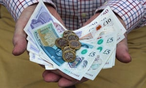 Pound coins and British pound notes in man's hands