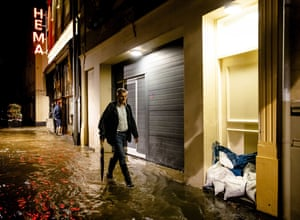 A person wearing rubber boots walks near sandbags in front of a door in the municipality of Valkenburg aan de Geul in the Netherlands. Streets have been flooded due to rising water from the Geul River