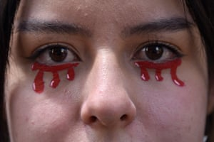 A protester with tears of blood painted on her face in Bogotá