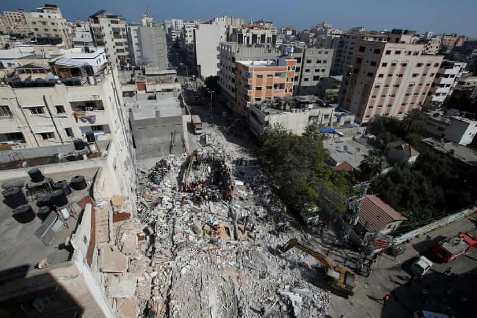 Rescuers search for people in the rubble of a building at the site of Israeli airstrikes.