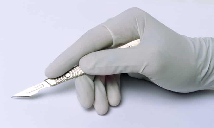 A hand in a surgical glove holding a scalpel