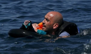Syrian refugee holding a baby in a lifetube swims towards the shore of Lesbos after their dinghy deflated some 100 metres away.
