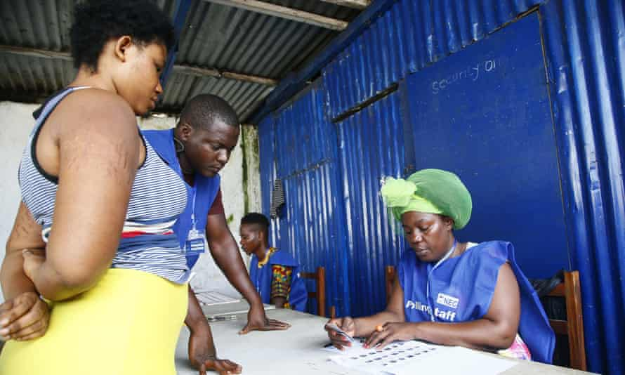 Polling staff in Monrovia, the Liberian capital, check a voter's name and ID.