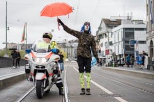 Zurich, Switzerland A man dressed as a clown holds an umbrella over a police officer