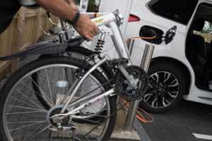David Kidd folds up his bike while his Mitsubishi Outlander charges.