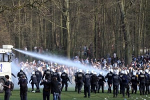 Bystanders and demonstrators are soaked by a Belgian police water cannon at Bois de la Cambre park in Brussels