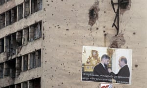 A poster on a bullet-riddled wall in Grozny showing Vladimir Putin presenting a medal to the Chechen leader, Ramzan Kadyrov.