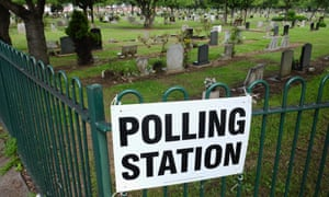 A polling station sign is attached to railings next to a cemetery in Redcar