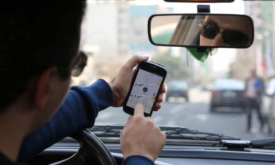 A Snapp driver checks the app on his mobile in Tehran.