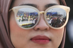 Kuala Lumpur, Malaysia: A woman's sunglasses reflect schoolchildren performing during 60th anniversary celebrations of Malaysian independence