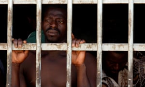 A man looks out of a barred door at a detention centre for migrants in Gharyan, Libya.