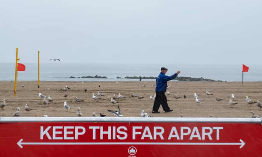 A man in a protective mask feeds seagulls at New York's Coney Island beach over Memorial Day weekend.