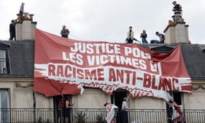Residents try to remove a banner installed on the roof by a far right group,