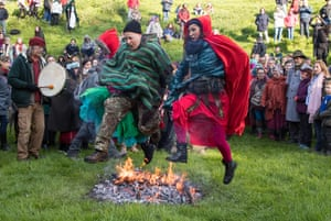 People jump over a fire as they gather in the Chalice Well Trust Gardens, which sit below Glastonbury Tor, for a sunrise ceremony