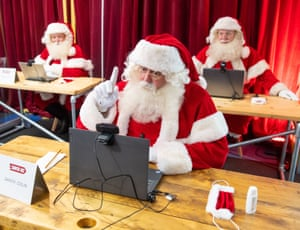 People dressed as Father Christmas practice making virtual calls to children at the launch of Santa HQ.