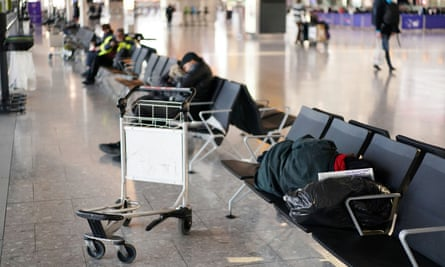 People are seen sleeping on the chairs at Heathrow airport