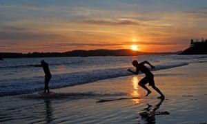Surfers on Tofino's Long Beach on Vancouver Island, British Columbia