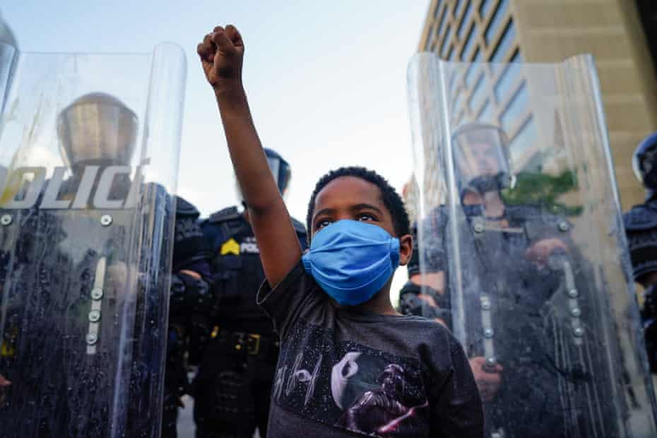 A young boy raises his fist for a photo by a family friend during a demonstration in Atlanta, Georgia.