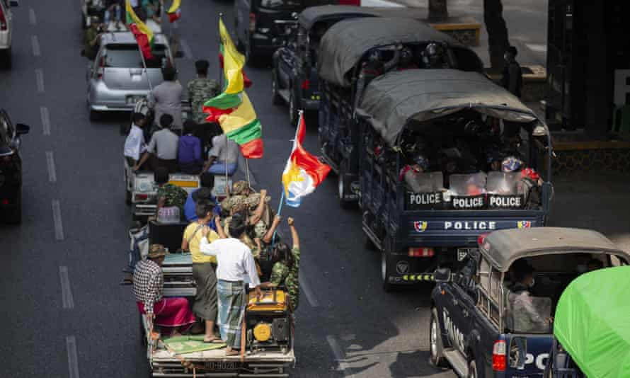Supporters of the Myanma military drive by police trucks parked in Yangon.