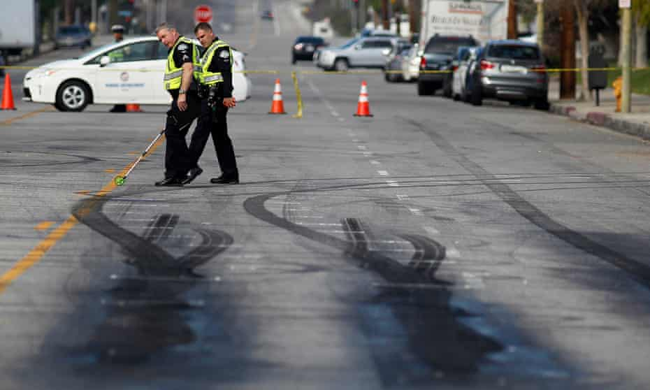 Police investigators survey skid marks at drag racing scene where two pedestrians were killed in Chatsworth, California.