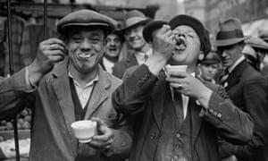 Two men enjoy jellied eels in a Whitechapel street in the 1920s.