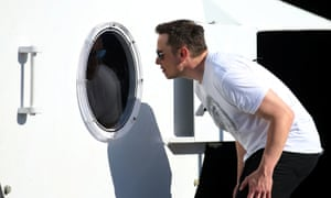 Elon Musk peers into a porthole at the SpaceX headquarters in Los Angeles