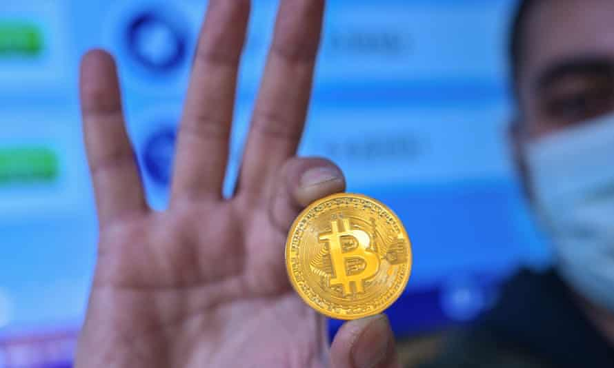 A man holds a physical imitation of a Bitcoin at a cryptocurrency exchange near the Grand Bazaar, Istanbul.