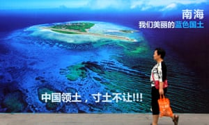 """A woman walks past a billboard in Shandong province in China. The text reads: """"South China Sea, our beautiful motherland, we won't let go an inch."""""""