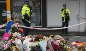 Police officers stand guard at a makeshift memorial near the Linwood mosque in Christchurch
