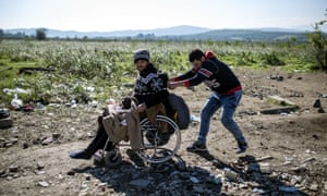 Two men wait to enter a registration camp near Gevgelija after crossing the Greece-Macedonia border