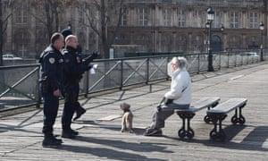 Police speak to a woman at Pont des Arts on April 04, 2020 in Paris, France.