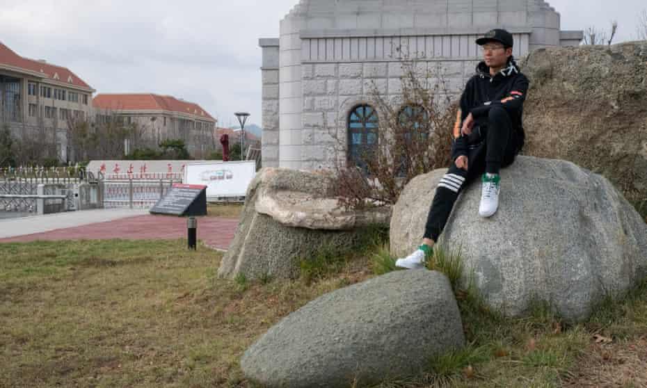 Yuan Yunsheng sitting on rocks at Shandong University campus, China.