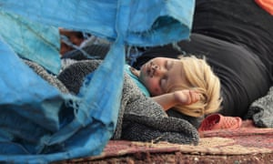 A displaced Syrian child sleeps on a mat laid out on the floor in an olive grove in Idlib province, Syria