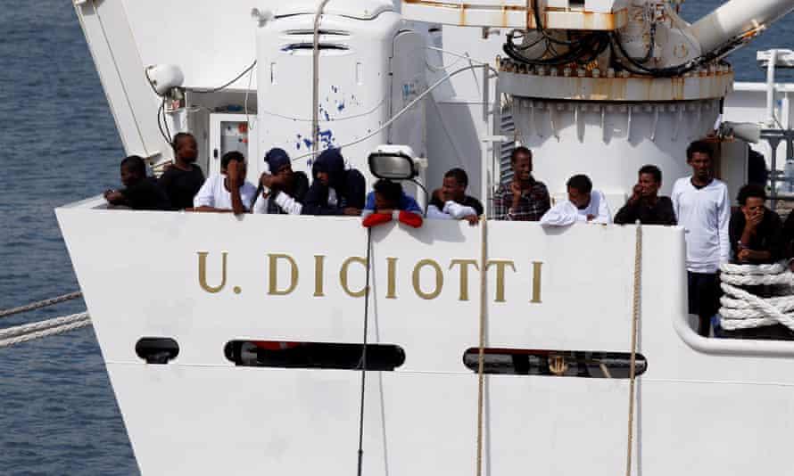 People wait to disembark from the Italian coastguard vessel Diciotti in Catania, Sicily.