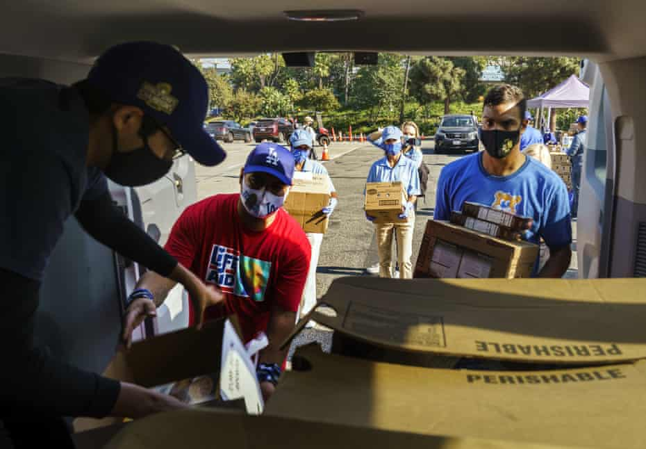 Volunteers help Bresee youth center volunteer, Luis Alarcon, far left, load his foundation's van with Thanksgiving supplies at a food drive-thru for not-for-profit community organizations at Dodger Stadium parking lot in Los Angeles Thursday, Nov. 19, 2020.