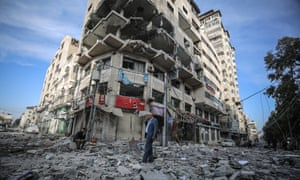 People seen among the debris of damaged Al-Gussin apartment after the Israeli army carried out airstrikes in Gaza.