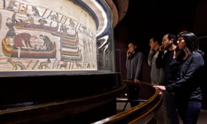 Visitors stand in front of the Bayeux tapestry at the Bayeux museum, France.