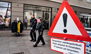 Officers of the Danish North Jutland Police walk behind a warning sign calling on people to keep distance to each other as they patrol in connection with the enforcement of the social distancing rules at the reopening of businesses, in a pedestrian zone and living area in Aalborg, Denmark, 28 April 2020
