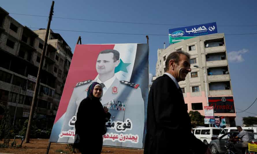 People walk in front of a billboard of the Syrian president, Bashar al-Assad, in Syria.